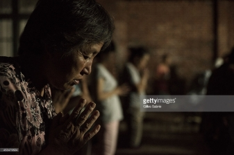 "YUTONG, HENAN, CHINA - 2014/08/05: A follower of Father Dong's ""underground"" Catholic church praying during the daily evening mass held in a yard. Not belonging to the Chinese Patriotic association, they don't have a real church for the gathering. Currently they have no place to go and have chosen this open air yard for the services. Millions of Catholics in China outside the patronage of the government controlled Chinese Patriotic Catholic Association. These ""underground"" catholic who recognized the Vatican as the only religious authority when it comes to their faith, are under the threat of harassment and imprisonment by the Chinese. authorities. (Photo by Gilles Sabrie/LightRocket via Getty Images)"