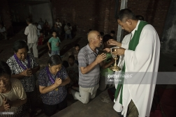 "YUTONG, HENAN, CHINA - 2014/08/05: Father Dong an ""underground"" Catholic priest, who has so far refused to join the Chinese Patriotic Catholic Association, unlike most catholic clerics in the region, giving the holy communion to some of his followers during the daily mass held in a yard. He doesn't have a real church for the gathering has chosen this open air yard for the celebrations. Millions of Catholics in China outside the patronage of the government controlled Chinese Patriotic Catholic Association. These ""underground"" catholic who recognized the Vatican as the only religious authority when it comes to their faith, are under the threat of harassment and imprisonment by the Chinese authorities. (Photo by Gilles Sabrie/LightRocket via Getty Images)"