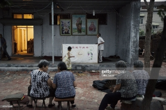 "YUTONG, HENAN, CHINA - 2014/08/05: Parishioners of Father Dong's ""underground"" Catholic church have started to gather for the daily evening mass held in a yard. Not belonging to the Chinese Patriotic association, they don't have a real church for the gathering. Currently they have no place to go and have chosen this open air yard for the services. Millions of Catholics in China outside the patronage of the government controlled Chinese Patriotic Catholic Association. These ""underground"" catholic who recognized the Vatican as the only religious authority when it comes to their faith, are under the threat of harassment and imprisonment by the Chinese. authorities. (Photo by Gilles Sabrie/LightRocket via Getty Images)"