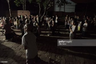 "YUTONG, HENAN, CHINA - 2014/08/05: Followers of Father Dong's ""underground"" Catholic church praying during the daily evening mass held in a yard. Not belonging to the Chinese Patriotic association, they don't have a real church for the gathering. Currently they have no place to go and have chosen this open air yard for the services. Millions of Catholics in China outside the patronage of the government controlled Chinese Patriotic Catholic Association. These ""underground"" catholic who recognized the Vatican as the only religious authority when it comes to their faith, are under the threat of harassment and imprisonment by the Chinese. authorities. (Photo by Gilles Sabrie/LightRocket via Getty Images)"