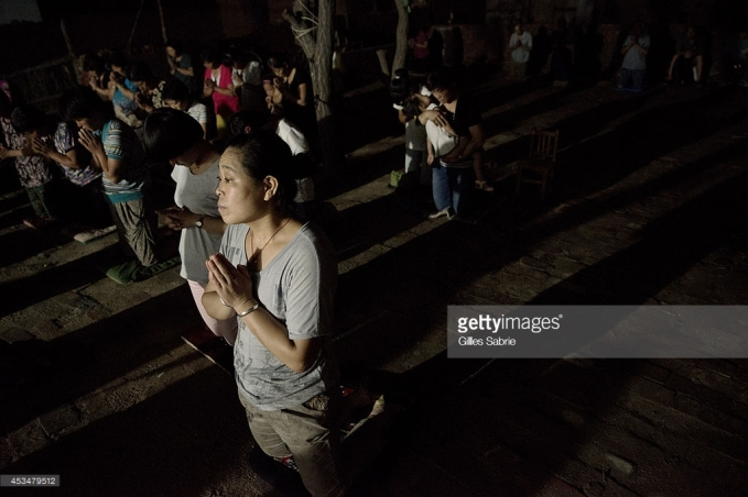 "YUTONG, HENAN, CHINA - 2014/08/05: A follower of Father Dong's ""underground"" Catholic church praying during the daily evening mass held in a yard. Not belonging to the Chinese Patriotic association, they don't have a real church for the gathering. Currently they have no place to go and have chosen this open air yard for the services. Millions of Catholics in China outside the patronage of the government controlled Chinese Patriotic Catholic Association. These ""underground"" catholic who recognized the Vatican as the only religious authority when it comes to their faith, are under the threat of harassment and imprisonment by the Chinese authorities. (Photo by Gilles Sabrie/LightRocket via Getty Images)"